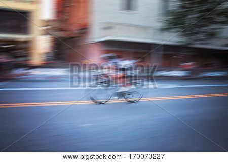 a person on a bicycle in a race held downtown in a city taken with a long shutter speed to create motion blur, toned with a retro vintage instagram filter effect action or app