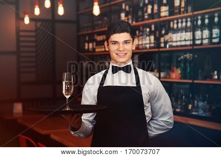 Male waiter holding tray with champagne in cafe