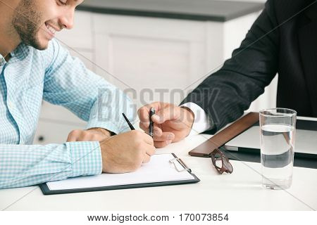 Man signing documents at notary office