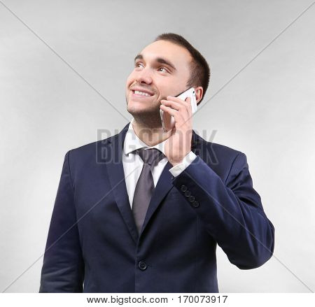 Handsome man talking by mobile phone, on light background