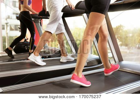 Young people running on treadmills in gym, close up view