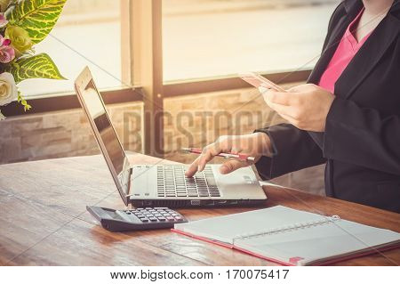 Close up of business woman's hand on a keyboard and holding a smart phone