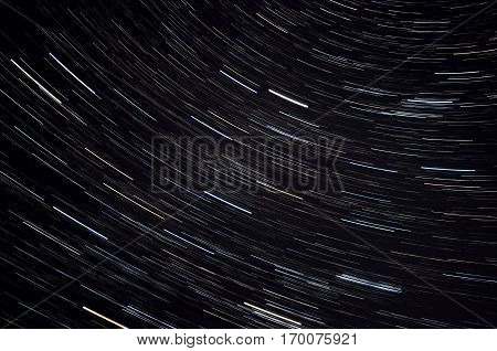 Abstract decorative space background with traces of stars in the form of tracks against the black night sky