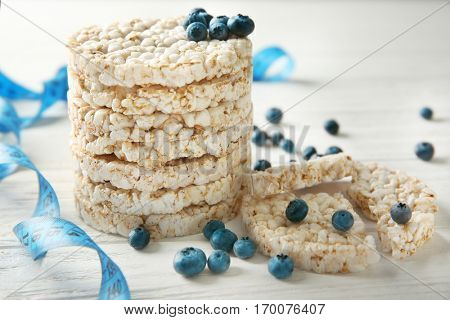 Round rice crispbreads with blueberries and measuring tape, closeup
