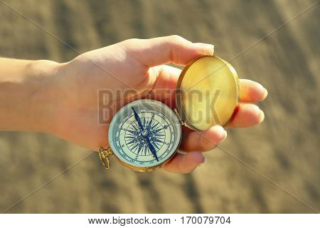 Female hand holding compass on blurred countryside road background