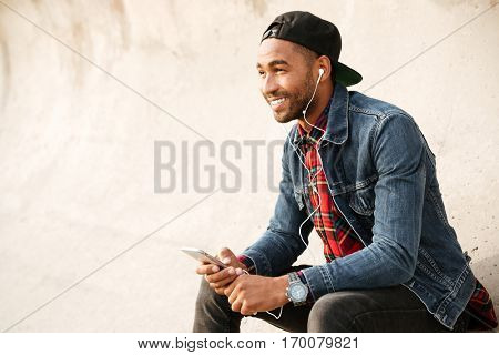 Cheerful african young man wearing cap walking on the beach and chatting by his phone while listening music with earphones.