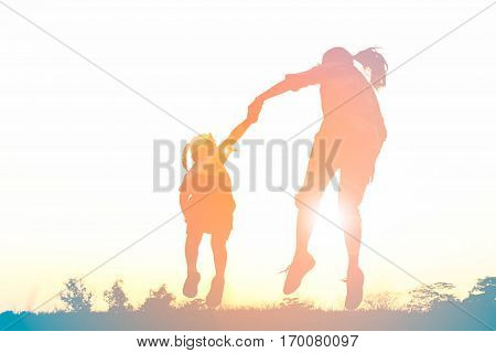 Silhouette of happy family jumping together on the park at sunset