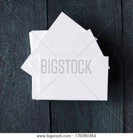 A sqaure photo of a stack of blank white thick cardboard business cards on a dark wooden background texture. A mockup or a minimalist banner with copyspace