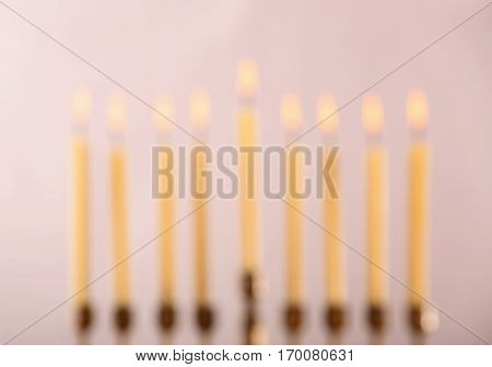 Blurred view of menorah with candles for Hanukkah on light background, close up
