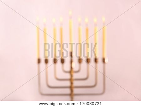 Blurred view of menorah with candles for Hanukkah on light background