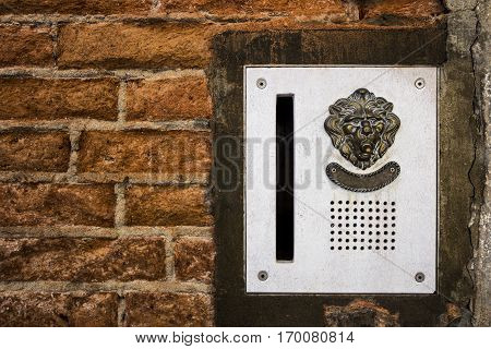 brass doorplate and doorbell in a shape of a lion's head on an old, cracked brick wall , Venice, Italy