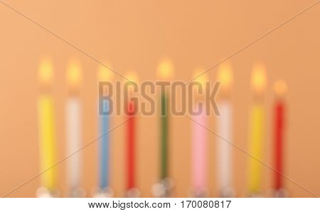 Blurred view of nine burning candles on color background. Hanukkah concept