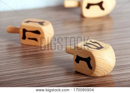 Dreidel for Hanukkah on wooden table, close up