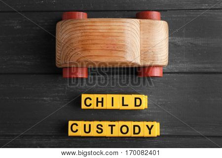 Text CHILD CUSTODY made of yellow blocks with toy car on dark wooden background, closeup