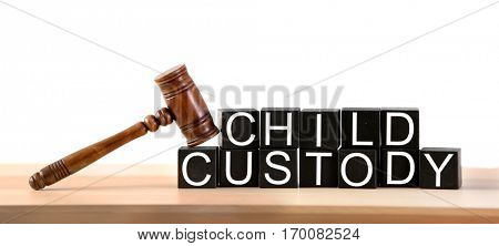 Text CHILD CUSTODY made of black blocks with judge gavel on table against white background, closeup