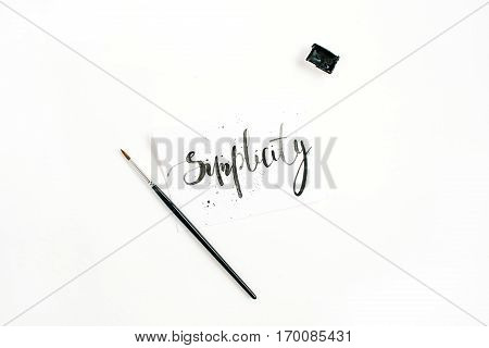 Minimalistic stylish composition with word Simplicity written in calligraphic style on paper with paint brush on white background. Flat lay top view
