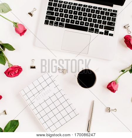 Workspace with laptop red roses flowers coffee cup notebook and clips on white background. Flat lay top view. Feminine background.