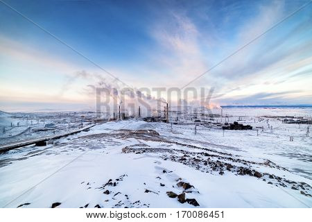 Winter landscape with the smoking pipes of steel works. Winter landscape Arctic tundra