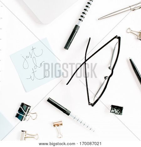 White office desk frame with quote Just Do It and supplies. Laptop pen clips glasses and office supplies on white background. Flat lay top view mockup.
