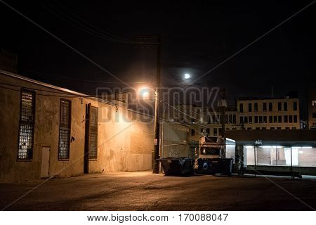 Dark urban city alley at night with moon, truck, dumpsters and loading dock