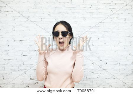 Fashionable Woman In Sunglasses Suprised And Shocked In White Vintage Brick Wall