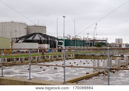 Air bubbling through foul water in an aeration tank and large containers for methane and other gasses at Deephams Sewage Treatment Works in Edmonton North London. Viewed on a cloudy day in early Autumn.