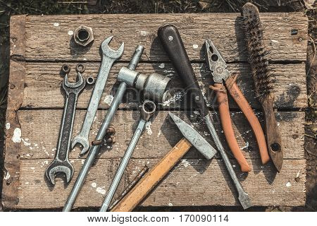 On weathered old wooden surface lie the old, oily wrenches, pliers, screwdrivers and metal brush. Near scattered old rusty nuts.