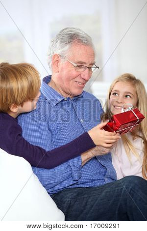 Kids giving birthday gift to their grandfather