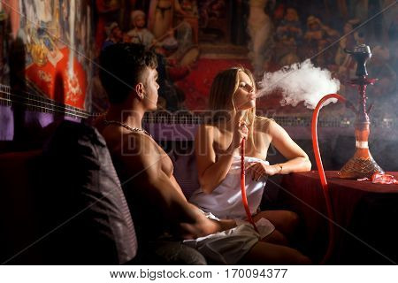 Young beautiful romantic couple relaxing together at spa while sitting at turkish bath and smoking hookah