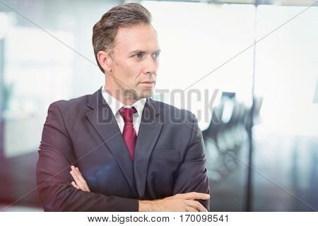 Businessman standing with arms crossed and looking away