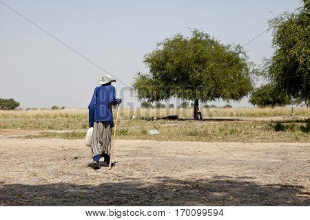 woman walking in grassland of South Sudan