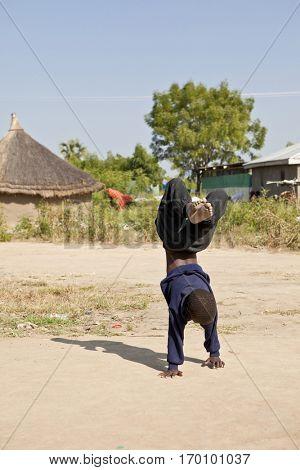 Boy doing handstand in village in South Sudan
