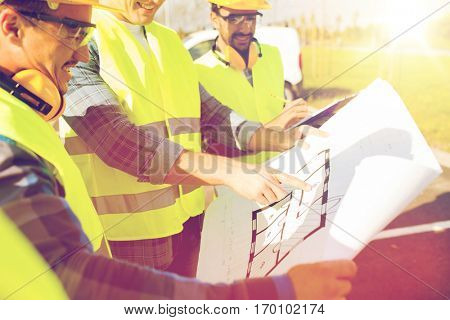 building, construction, development, teamwork and people concept - close up of builders high visible vests with blueprint at building site