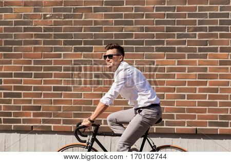 lifestyle, transport and people concept - young man in sunglasses riding bicycle on city street over brickwall