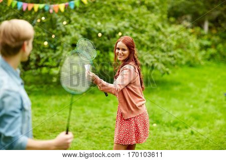 leisure, holidays, people and sport concept - happy couple or friends playing badminton or shuttlecock at summer garden