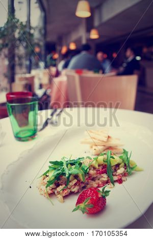 Seabass carpaccio on restaurant table, blurred people in background, toned image