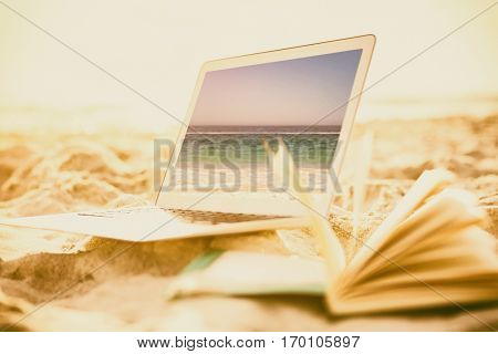 Open book and laptop on sand against waters edge at the beach