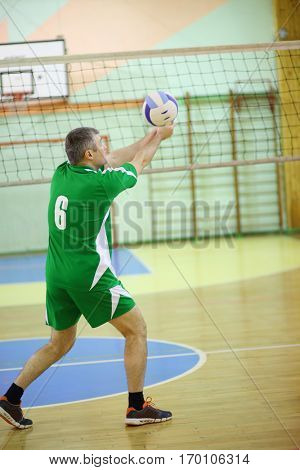 Middle age man trainer in green sport wear plays volleyball in gym