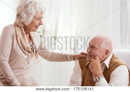 Older woman holding her hand on a man's shoulder
