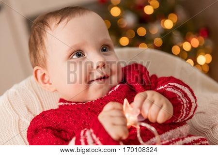 Christmas time. Cute baby plays with the lights decorations, Christmas tree in the background