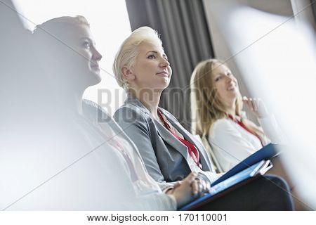 Smiling businesswomen attending seminar