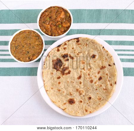 Indian food roti, a traditional and popular bread made from wheat flour dough, and two vegetable curries as side dishes.