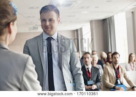 Confident businessman looking at public speaker during seminar