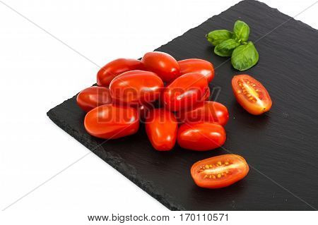 Small red oblong tomatoes on plate. Studio Photo