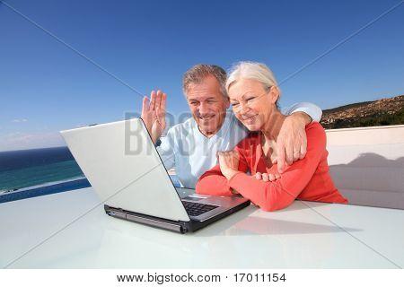 Senior couple waving at web-camera on laptop computer