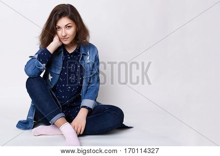 A pretty girl with dark hair and charming brown eyes wearing stylish jean clothes sitting crossed legs on the white floor in the studio being relaxed and pleased looking attentively into camera