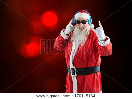 Rock n roll santa claus listening to music on headphones against red background