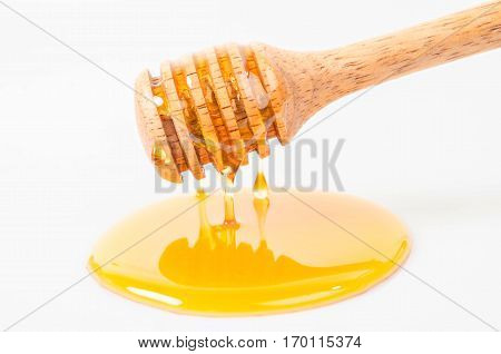 Honey dripping with honey stick isolated on a white background.