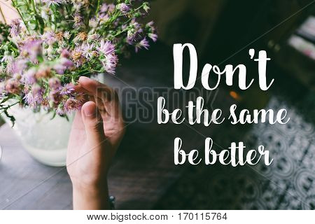 Life quote. Motivation quote on soft background. The hand touching purple flowers. Don't be the same be better.