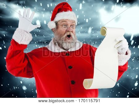 Santa claus reading wish list against snowy background